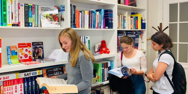 three young girls in front of library book shelves reading test preparation books